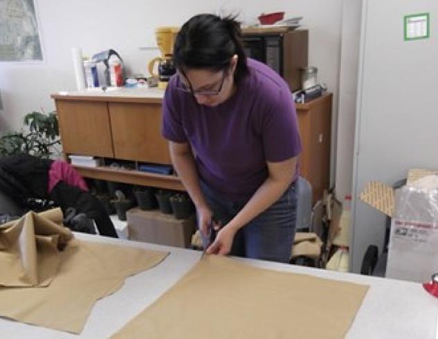 Alexandra Hetrick cutting material for dance dresses in Nanwalek.